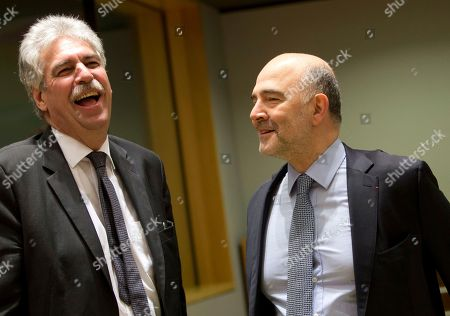 Austrian Finance Minister Hans Joerg Schelling, left, speaks with European Commissioner for Economic and Financial Affairs Pierre Moscovici during a meeting of eurogroup finance ministers at the Europa building in Brussels on . Finance ministers from countries using the euro single currency meet Monday to discuss Greece's debt-laden economy and their budgetary plans for 2017