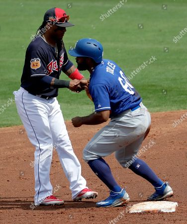 Los Angeles Dodgers right fielder Andrew Toles (60) is helped up after being forced out at second by Cleveland Indians' Michael Martinez during the second inning of a spring training baseball game, in Goodyear, Ariz