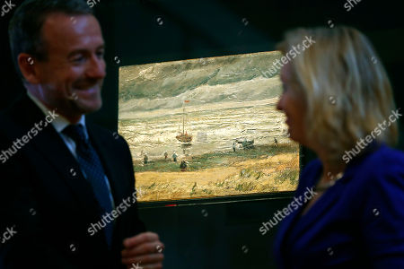 """Van Gogh Museum director Axel Rueger, left, and Jet Bussemaker, Minister for Education, Culture and Science, stand next to the stolen and recovered """"Seascape at Scheveningen"""" by Dutch master Vincent van Gogh, during a press conference in Amsterdam, Netherlands, . Two paintings by Vincent van Gogh titled """"Seascape at Scheveningen"""" (1882) and """"Congregation leaving the Reformed Church in Nuenen,"""" (1884-1885) returned to the Amsterdam museum after they were stolen from in a nighttime heist 15 years ago and recovered by Naples police in Italy"""