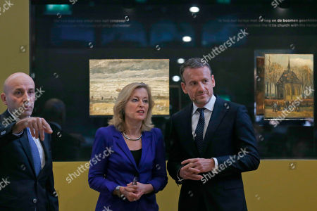 """General Gianluigi D'Alfonso of the Italian Guardia Di Finanza, Jet Bussemaker, Minister for Education, Culture and Science and Van Gogh Museum director Axel Rueger, from left, pose in front of two stolen and recovered van Gogh paintings during a press conference in Amsterdam, Netherlands, . The two paintings by Dutch master Vincent van Gogh titled """"Seascape at Scheveningen"""" (1882) and """"Congregation leaving the Reformed Church in Nuenen,"""" (1884-1885) returned to the Amsterdam museum after they were stolen from in a nighttime heist 15 years ago and recovered by Naples police in Italy"""
