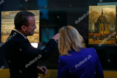 """Stock Photo of Van Gogh Museum director Axel Rueger, left, and Jet Bussemaker, Minister for Education, Culture and Science, look at two stolen and recovered paintings by Dutch master Vincent van Gogh during a press conference in Amsterdam, Netherlands, . The two paintings titled """"Seascape at Scheveningen"""", left, (1882) and """"Congregation leaving the Reformed Church in Nuenen,"""" (1884-1885) returned to the Amsterdam museum after they were stolen from in a nighttime heist 15 years ago and recovered by Naples police in Italy"""