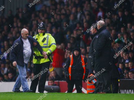 A Blackburn Rovers Fan is Removed From the Pitch by A Police Officer Behind Manager Steve Kean United Kingdom Blackburn
