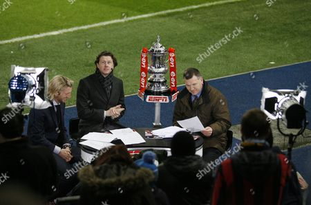 The Fa Cup Trophy is Positioned On an Espn Stand Next to Presenters Ray Stubbs Steve Mcmanaman and Robbie Savage United Kingdom Manchester