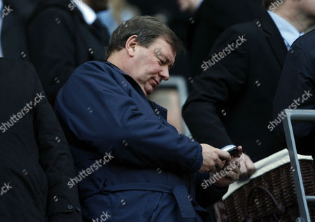Chief Executive Officer of Portsmouth Peter Storrie Studies His Mobile Phone Up in the Stand United Kingdom Manchester