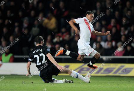 Alex Chamberlain of Southampton Hurdles A Challenge From John O'shea of Manchester United United Kingdom Southampton