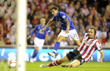 Stock Image of Tim Cahill of Everton Shoots at Goal As Sotirios Kyrgiakos of Sunderland Tackles United Kingdom Sunderland