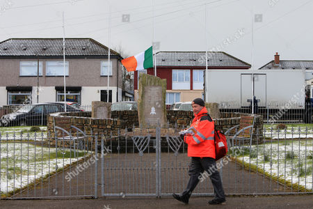 A postman walks past an Irish flag flying at half mast at a Irish Republican memorial  in the Creagan area of Derry, Northern Ireland, 21 March 2017. Sinn Fein's Martin McGuinness, Northern Ireland's former deputy first minister, has died aged 66. It is understood he had been suffering from a rare heart condition. The former IRA leader turned peacemaker worked at the heart of the power-sharing government following the 1998 Good Friday Agreement. He became deputy first minister in 2007, standing alongside Democratic Unionist Party leaders Ian Paisley, Peter Robinson and Arlene Foster.