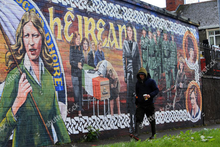 A man walks past an old Irish Republican mural close to the home of Martin McGuinness in the Bogside area of Derry, Northern Ireland, 21 March 2017. Sinn Fein's Martin McGuinness, Northern Ireland's former deputy first minister, has died aged 66. It is understood he had been suffering from a rare heart condition. The former IRA leader turned peacemaker worked at the heart of the power-sharing government following the 1998 Good Friday Agreement. He became deputy first minister in 2007, standing alongside Democratic Unionist Party leaders Ian Paisley, Peter Robinson and Arlene Foster.