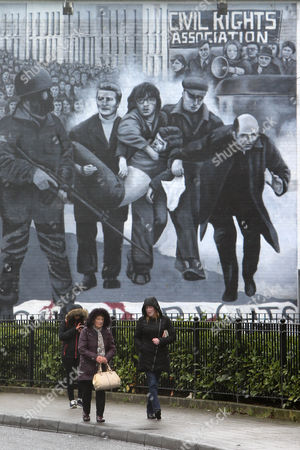 People walk past a Bloody Sunday mural close to the home of Martin McGuinness in the Bogside area of Derry, Northern Ireland, 21 March 2017. Sinn Fein's Martin McGuinness, Northern Ireland's former deputy first minister, has died aged 66. It is understood he had been suffering from a rare heart condition. The former IRA leader turned peacemaker worked at the heart of the power-sharing government following the 1998 Good Friday Agreement. He became deputy first minister in 2007, standing alongside Democratic Unionist Party leaders Ian Paisley, Peter Robinson and Arlene Foster.