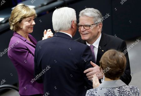 Former German President Joachim Gauck, 2nd right, embraces his successor Frank-Walter Steinmeier, 2nd left, during a joint meeting of German parliamentarians in Berlin, Germany,. At left its Gauck's partner Daniela Schadt and at right Steinmeiers' wife Elke Buedenbender