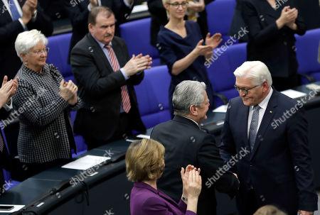German President Frank-Walter Steinmeier, right, shakes hands with Former German President Joachim Gauck, center, after Steinmeier's speech during a joint meeting of German parliamentarians in Berlin, Germany,. Standing at left is Gauck's partner Daniela Schadt