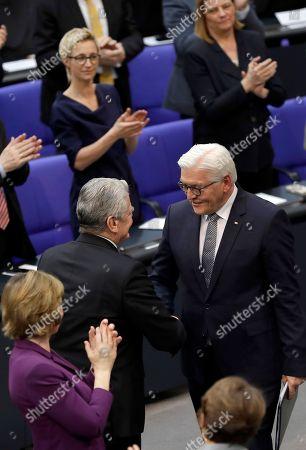 German President Frank-Walter Steinmeier, right, shakes hands with Former German President Joachim Gauck, left, after Steinmeier's speech during a joint meeting of German parliamentarians in Berlin, Germany,. Standing at left is Gauck's partner Daniela Schadt