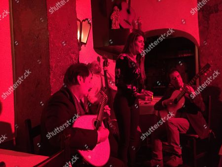 This photo shows singer Cuca Roseta, (standing), bathed in red light during a fado performance at Clube de Fado in Lisbon, accompanied on the left by Mario Pacheco on the 12-string Portuguese guitar and another musician on the right playing a conventional guitar. Lisbon is home to numerous clubs where fado, a soulful, melancholy genre of Portuguese folk music, is performed nightly