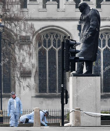 A policeman looks up at the statue of, British War time leader, Winston Chruchill, as police forensic teams search Parliament Square outside the Houses of Parliament in London, Britain 23 March 2017. Scotland Yard said on 23 March 2017 that police have made seven arrests in raids carried out over night in Birmingham London and elsewhere in the country after the terror attack in the Westminister Palace grounds and on Westminster Bridge on 22 March 2017 leaving four people dead, including the attacker, and 29 people injured.
