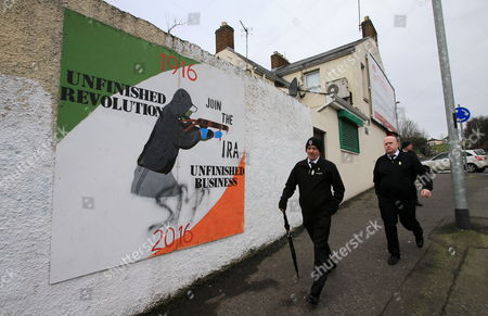 People walk pass a IRA mural in the Bogside area of Londonderry, Northern Ireland, 23 March 2017 ahead of the funeral of Sinn Féin's Martin McGuinness. Sinn Fein's Martin McGuinness, Northern Ireland's former deputy first minister, died aged 66 on 21 March 2017. It is understood he had been suffering from a rare heart condition. The former IRA leader turned peacemaker worked at the heart of the power-sharing government following the 1998 Good Friday Agreement. He became deputy first minister in 2007, standing alongside Democratic Unionist Party leaders Ian Paisley, Peter Robinson and Arlene Foster.