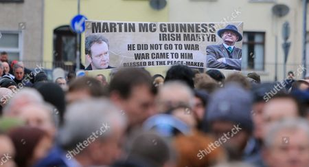 People walk with a banner of Martin McGuiness in the Bogside area of Londonderry, Northern Ireland, 23 March, 2017 ahead of the funeral of Sinn Fein's late leader. Sinn Fein's Martin McGuinness, Northern Ireland's former deputy first minister, died aged 66 on 21 March 2017. It is understood he had been suffering from a rare heart condition. The former IRA leader turned peacemaker worked at the heart of the power-sharing government following the 1998 Good Friday Agreement. He became deputy first minister in 2007, standing alongside Democratic Unionist Party leaders Ian Paisley, Peter Robinson and Arlene Foster.