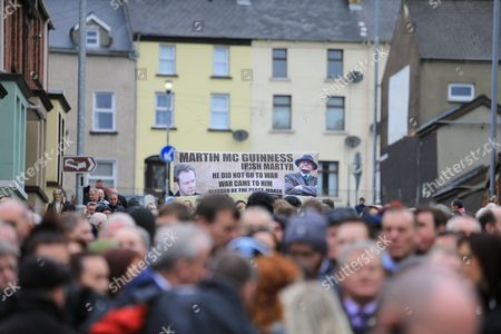 People carry a banner showing Martin McGuiness in the Bogside area of Londonderry, Northern Ireland, 23 March, 2017 ahead of the funeral of Sinn Fein's late leader. Sinn Fein's Martin McGuinness, Northern Ireland's former deputy first minister, died aged 66 on 21 March 2017. It is understood he had been suffering from a rare heart condition. The former IRA leader turned peacemaker worked at the heart of the power-sharing government following the 1998 Good Friday Agreement. He became deputy first minister in 2007, standing alongside Democratic Unionist Party leaders Ian Paisley, Peter Robinson and Arlene Foster.