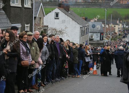 People gather along the road in the Bogside area of Londonderry, Northern Ireland, 23 March 2017, ahead of the funeral of Martin McGuinness. Sinn Fein's Martin McGuinness, Northern Ireland's former deputy first minister, died aged 66 on 21 March 2017. It is understood he had been suffering from a rare heart condition. The former IRA leader turned peacemaker worked at the heart of the power-sharing government following the 1998 Good Friday Agreement. He became deputy first minister in 2007, standing alongside Democratic Unionist Party leaders Ian Paisley, Peter Robinson and Arlene Foster.