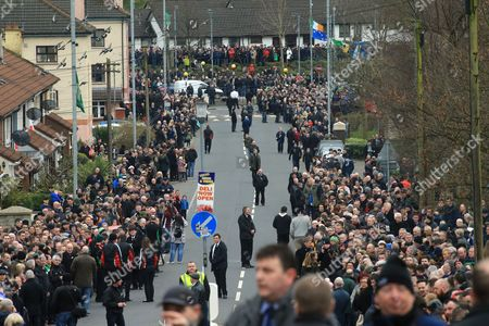 People gather along the road in the Bogside area of Londonderry, Northern Ireland, 23 March 2017, ahead of the funeral of Sinn Fein's late leader. Sinn Fein's Martin McGuinness, Northern Ireland's former deputy first minister, died aged 66 on 21 March 2017. It is understood he had been suffering from a rare heart condition. The former IRA leader turned peacemaker worked at the heart of the power-sharing government following the 1998 Good Friday Agreement. He became deputy first minister in 2007, standing alongside Democratic Unionist Party leaders Ian Paisley, Peter Robinson and Arlene Foster.