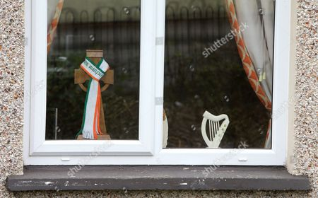 An Irish Harp and scarf are seen in a window in the Bogside area of Londonderry, Northern Ireland,  23 March 2017, ahead of the funeral of Sinn Fein's late leader. Sinn Fein's Martin McGuinness, Northern Ireland's former deputy first minister, died aged 66 on 21 March 2017. It is understood he had been suffering from a rare heart condition. The former IRA leader turned peacemaker worked at the heart of the power-sharing government following the 1998 Good Friday Agreement. He became deputy first minister in 2007, standing alongside Democratic Unionist Party leaders Ian Paisley, Peter Robinson and Arlene Foster.
