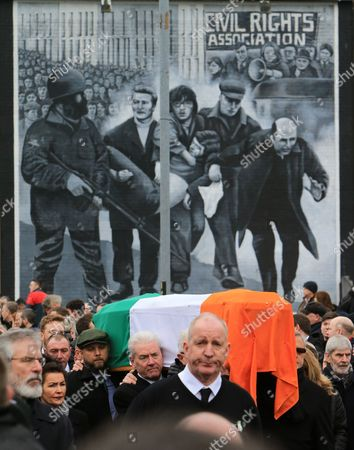 The coffin of Martin McGuinness is carried pass the 'Bloody Sunday' mural in Londonderry, Northern Ireland, 23 March 2017, during the funeral of the late Sinn Fein leader. On far left is Sinn Fein President Gerry Adams. Sinn Fein's Martin McGuinness, Northern Ireland's former deputy first minister, died aged 66 on 21 March 2017. It is understood he had been suffering from a rare heart condition. The former IRA leader turned peacemaker worked at the heart of the power-sharing government following the 1998 Good Friday Agreement. He became deputy first minister in 2007, standing alongside Democratic Unionist Party leaders Ian Paisley, Peter Robinson and Arlene Foster.