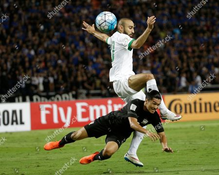 Mohammad Al-Sahlawi of Saudi Arabia, top, and Adison Promrakof Thailand, jump for the ball during their World Cup qualifiers soccer match at Rajamangala national stadium in Bangkok, Thailand
