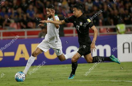 Salman Al-Faraj of Saudi Arabia, left, and Tanaboon Kesarat of Thailand battles for the ball during their World Cup qualifier soccer match at Rajamangala national stadium in Bangkok, Thailand