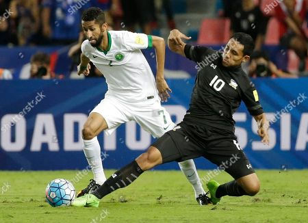Salman Al-Faraj of Saudi Arabia, left, and Teerasil Dangda of Thailand battles for the ball during their World Cup qualifier soccer match at Rajamangala national stadium in Bangkok, Thailand