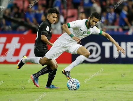 Salman Al-Faraj of Saudi Arabia, right, and Chanathip Songkrasin of Thailand battles for the ball during their World Cup qualifier soccer match at Rajamangala national stadium in Bangkok, Thailand