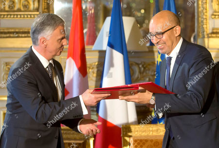 Swiss Federal Councillor Didier Burkhalter, left, and French State Secretary for European Affairs Harlem Desir exchange documents during a signing ceremony of an agreement on tax system for the EuroAirport Basel-Mulhouse-Freiburg in Paris, France