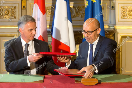 Swiss Federal Councillor Didier Burkhalter, left, and French State Secretary for European Affairs Harlem Desir exchange documents during a signing ceremony of an agreement on tax system for the EuroAirport Basel-Mulhouse-Freiburg in Paris, Thursday, France