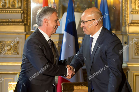 Stock Photo of Swiss Federal Councillor Didier Burkhalter, left, and French State Secretary for European Affairs Harlem Desir shake hands during a signing ceremony of an agreement on tax system for EuroAirport Basel Mulhouse Freiburg in Paris