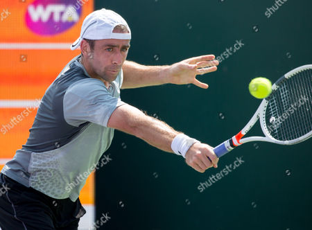 Stock Photo of Benjamin Becker, of Germany, hits a backhand against, Adrian Mannarino, of France, during a match at the Miami Open presented by Itau professional tennis tournament, played at Crandon Park Tennis Center in Key Biscayne, Florida, USA
