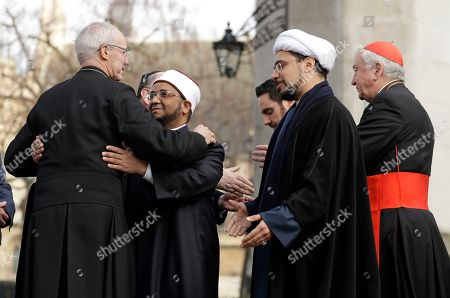 The Archbishop of Canterbury, Justin Welby, left, embraces Sheikh Ezzat Khalifa as Sheikh Mohammad al Hilli and Cardinal Vincent Nichols, Archbishop of Westminster, right, approach during a gathering of faith leaders take part in a vigil outside Westminster Abbey for the victims of Wednesday's attack in London