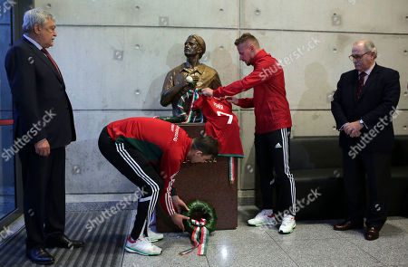 Hungary players Zoltan Gera, center left, and Balazs Dzsudzsak place a wreath and a jersey on a statue of late Hungarian player Miklos Feher at Benfica's Luz stadium in Lisbon . Feher died on the pitch while playing for Benfica in 2004. Hungary will play Portugal in a 2018 Russia World Cup Group B qualifying soccer match Saturday
