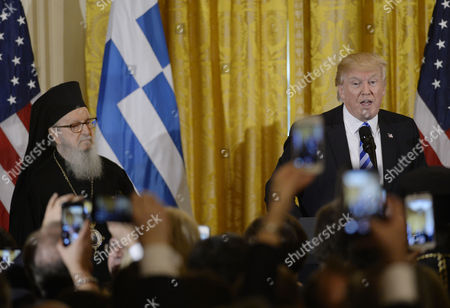 United States President Donald Trump speaks as Archbishop Demetrios of America of the Greek Orthodox Archdiocese of America looks on during an event to celebrate Greek Independence Day in the East Room the White House