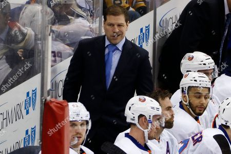 New York Islanders head coach Doug Weight stands behind his bench during an NHL hockey game against the Pittsburgh Penguins in Pittsburgh, . The Islanders won in a shootout, 4-3