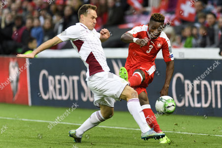 Latvia's Midfielder Aleksejs VisÅ?akovs (L) fights for the ball with Swiss defender Jacques Francois Moubandje during the 2018 Fifa World Cup Russia group B qualification soccer match between Switzerland and Latvia, at the stade de Geneve stadium, in Geneva, Switzerland, 25 March 2017.