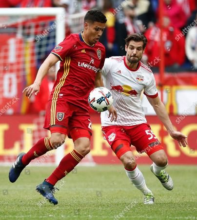 Real Salt Lake midfielder Luis Silva, left, tries to control the ball as New York Red Bulls defender Damien Perrinelle approaches during the first half of an MLS soccer match, in Harrison, N.J