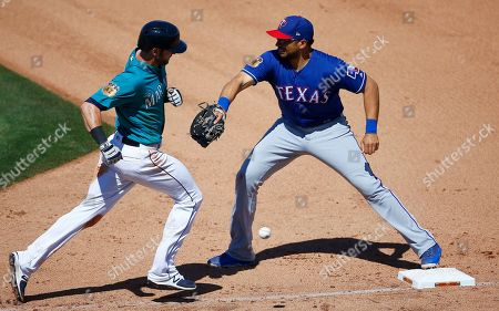 Stock Photo of Texas Rangers' James Loney, right, is unable to make the catch on a wide throw by Drew Robinson allowing Seattle Mariners' Mitch Haniger, left, to reach first base during the fourth inning of a spring training baseball game, in Peoria, Ariz