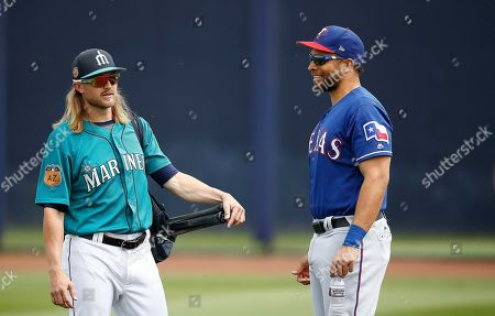 Stock Picture of Seattle Mariners' Taylor Motter, left, talks with Texas Rangers' James Loney, right, prior to a spring training baseball game, in Peoria, Ariz