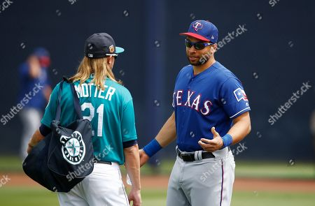 Texas Rangers' James Loney, right, talks with Seattle Mariners' Taylor Motter, left, prior to a spring training baseball game, in Peoria, Ariz