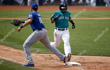 Texas Rangers' James Loney, left, beats Seattle Mariners' Rayder Ascanio, right, to first base for an out during the third inning of a spring training baseball game, in Peoria, Ariz