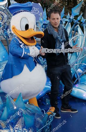 Marc-Olivier Fogiel poses with Disney character Donald Duck