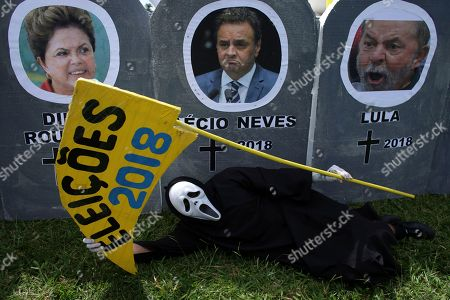 """A man dressed as the grim reaper lies in front of images of Brazil's former president Luiz Inacio Lula da Silva, right, the Senator Aecio Neves, center, and Brazil's former president Dilma Rousseff, during a protest against corruption in Brasilia, Brazil, . Members of the movement against corruption protested around the country and demanded the arrest of former president Lula da Silva and the end of campaign funding with money from corruption. The text on the scythe reads in Portuguese """"Elections 2018"""