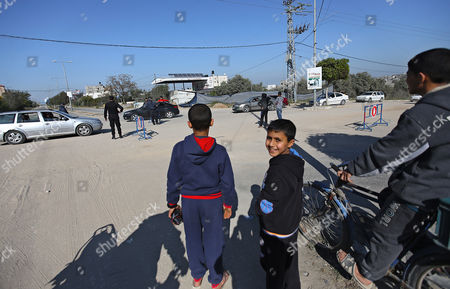 Palestinian boys watch Hamas security forces standing guard at the check point near Erez crossing point in Beit Hanun town in the northern Gaza Strip on, 26 March 2017. Erez crossing point has been closed after senior leader of Ezz Al-Din Al-Qassam brigades, the armed wing of the Palestinian Hamas movement, Mazen Al-Faqhaa was killed on 24 March 2017 after gunmen shot him dead near his home in Tal Al-Hawa neighbourhood.  Al-Faqhaa was freed by Israeli in 2011 prisoner swap with more than 1,000 other Palestinian prisoners in exchange for Gilad Shalit, an Israeli solder Hamas had detained for five years.