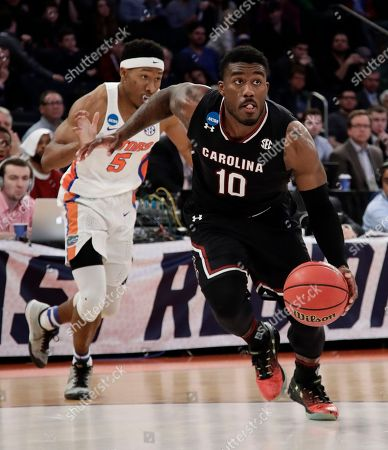 South Carolina guard Duane Notice (10) drives to the lane past Florida guard KeVaughn Allen (5) of the East Regional championship game of the NCAA men's college basketball tournament, in New York
