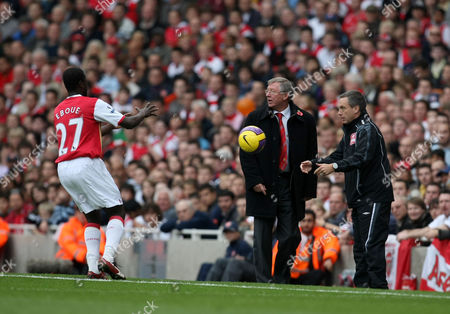 The fourth official Alan Wiley throws the ball back for Emmanuel Eboue of Arsenal, in front of Manchester United manager Sir Alex Ferguson