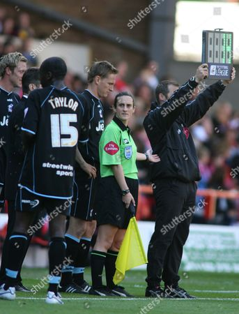 Referee' s Assistant Amy Rayner stands with players during a substitution