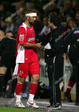 Swindon Town manager congratulates captain Christian Roberts after substituting him late on